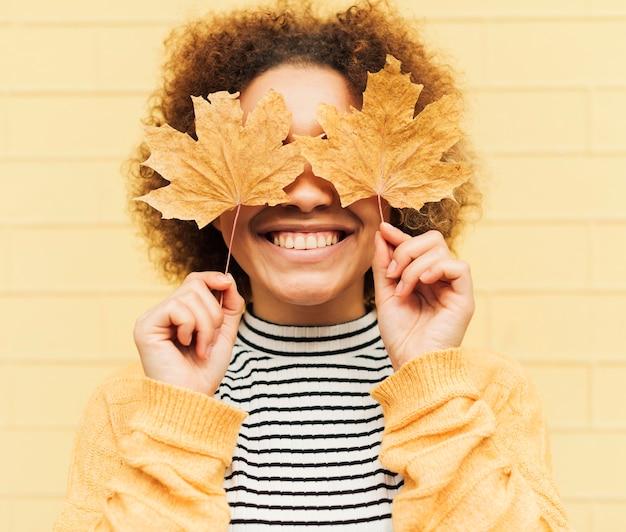 Retrato de mujer joven rizada que cubre sus ojos con hojas