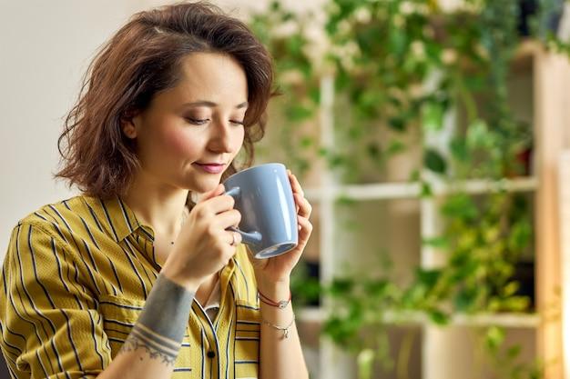Retrato de mujer joven en ropa casual comenzando su día con una taza de café o té de hierbas relajante