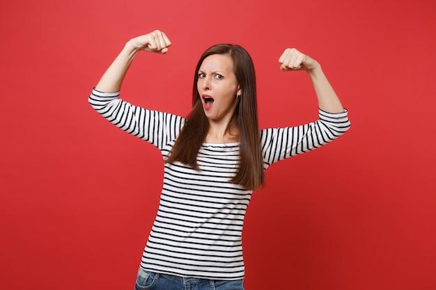 Retrato de mujer joven en ropa de rayas extendiendo las manos mostrando bíceps manteniendo la boca abierta