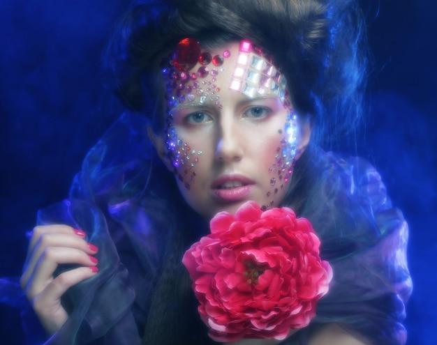 Retrato de mujer joven con rostro artístico sosteniendo una gran flor roja