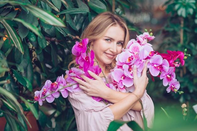Retrato de una mujer joven rubia abrazando las ramas de flores de orquídeas
