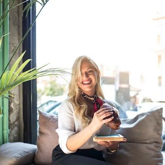 Retrato de una mujer joven rubia comiendo sándwich en la cafetería