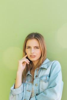 Retrato de una mujer joven rubia contemplada contra el telón de fondo verde menta