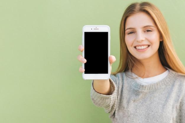 Retrato de una mujer joven rubia feliz que muestra el teléfono móvil contra el contexto verde
