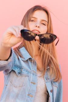 Retrato de una mujer joven rubia que sostiene las gafas de sol negras en la mano que mira la cámara