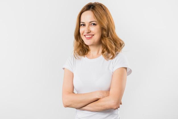 Retrato de una mujer joven rubia sonriente con los brazos cruzados