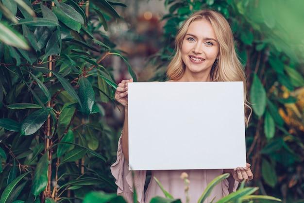 Retrato de una mujer joven rubia sonriente que se coloca en el vivero de la planta que muestra el cartel en blanco blanco