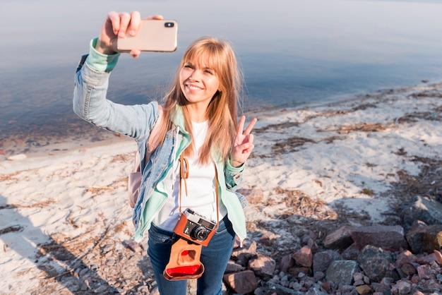 Retrato de una mujer joven rubia sonriente que hace el gesto de la paz que toma el selfie en el teléfono móvil
