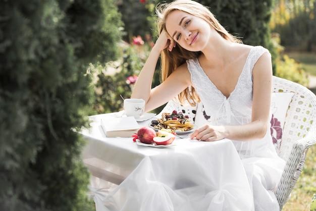 Retrato de una mujer joven rubia sonriente que se sienta cerca de la mesa de desayuno en el jardín