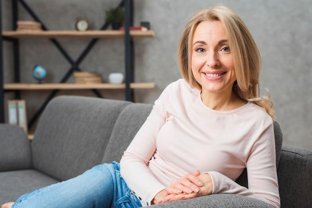 Retrato de una mujer joven rubia sonriente que se sienta en el sofá que mira la cámara
