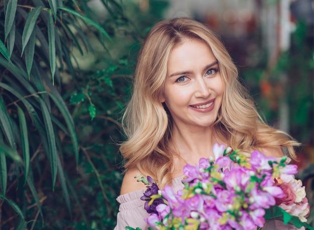 Retrato de una mujer joven rubia sonriente que sostiene el ramo de la flor