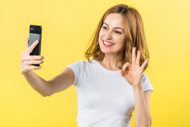 Retrato de una mujer joven rubia sonriente que toma el autorretrato en el teléfono móvil que hace gesto aceptable