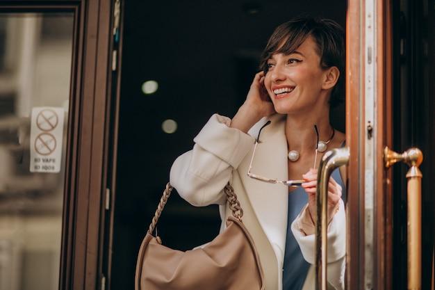 Retrato de mujer joven saliendo de las puertas en algún café