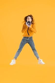 Retrato mujer joven saltando con megáfono