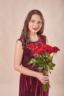 Retrato de mujer joven satisfecha en vestido rojo con ramo de rosas