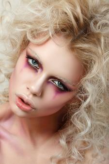 Retrato de mujer joven sensual con pelo rubio rizado y maquillaje de payaso de moda