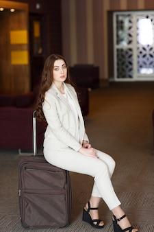 Retrato mujer joven sentada en maletas en la terminal o estación de tren, la mujer se reunió en un viaje.
