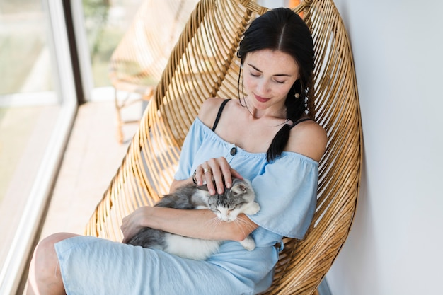 Retrato de mujer joven sentada en una silla acariciando a su gato