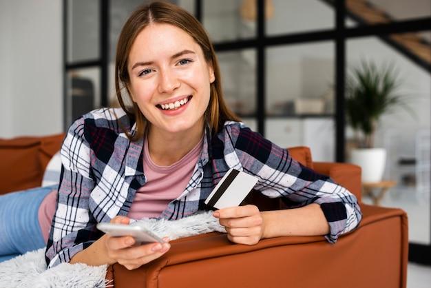 Retrato de mujer joven sentada en el sofá con teléfono