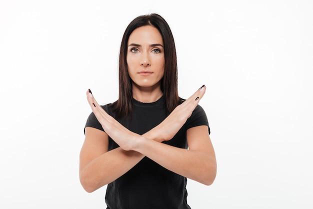 Retrato de una mujer joven seria que muestra gesto de manos cruzadas