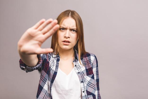 Retrato de una mujer joven seria que muestra gesto de la parada con su palma aislada sobre la pared gris.