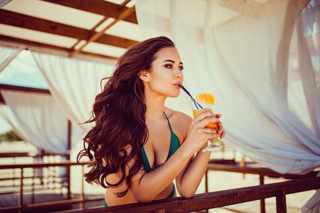 Retrato de mujer joven sexy en bikini con copa de cóctel naranja con paja y frutas posando en la barra de madera de la carpa con cortinas blancas