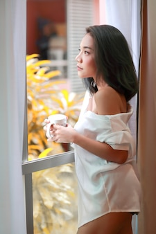 Retrato de mujer joven y sexy despierta y ve la vista desde la ventana del dormitorio