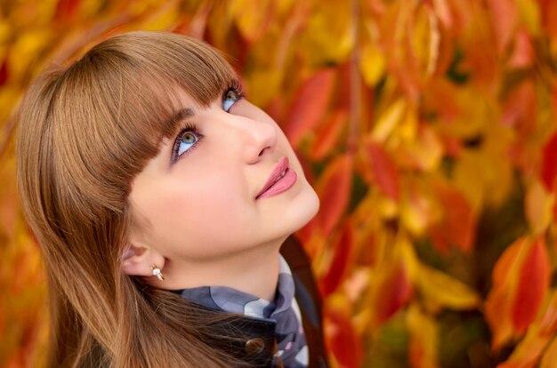 Retrato de una mujer joven sobre un fondo de hojas de otoño.