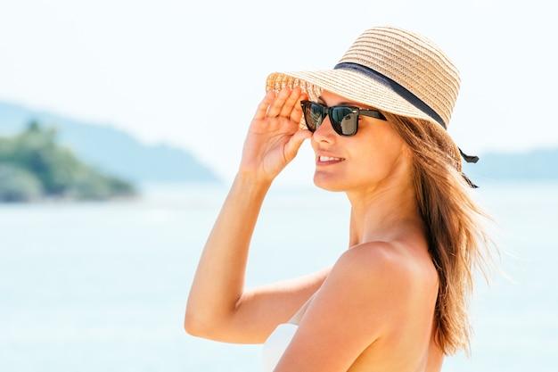Retrato mujer joven con un sombrero de paja en la playa