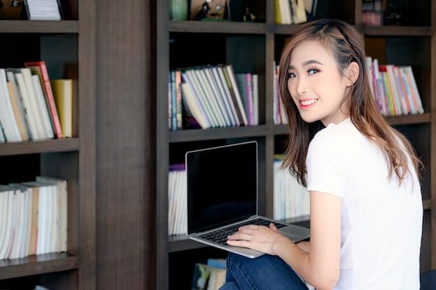 Retrato de mujer joven sonriendo en la biblioteca