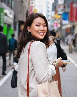 Retrato de mujer joven sonriendo en la calle