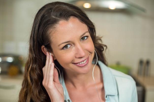 Retrato de mujer joven sonriendo mientras escucha música con auriculares