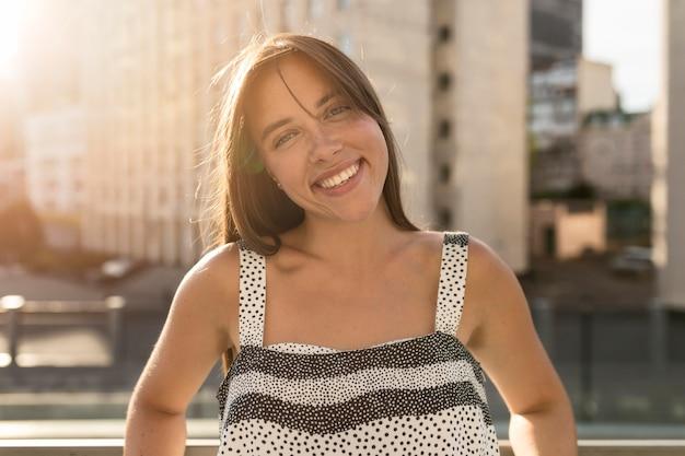 Retrato de mujer joven sonriendo mientras posa