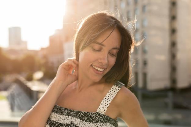 Retrato de mujer joven sonriendo mientras posando al aire libre