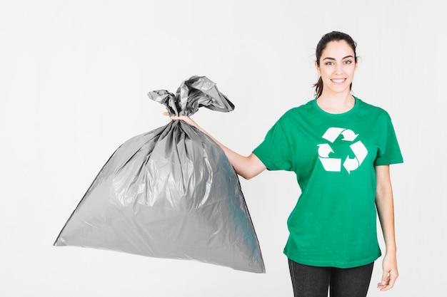 Retrato de una mujer joven sonriente con bolsa de basura