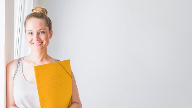 Retrato de mujer joven sonriente con carpeta amarilla