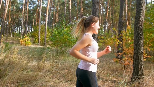 Retrato de mujer joven sonriente con cola de caballo corriendo en el bosque.