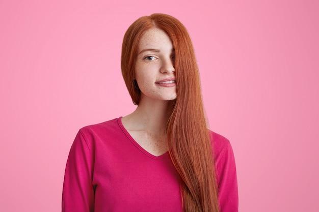 Retrato de mujer joven sonriente complacida con cabello largo y jengibre cubriendo su rostro, modelos para una conocida revista