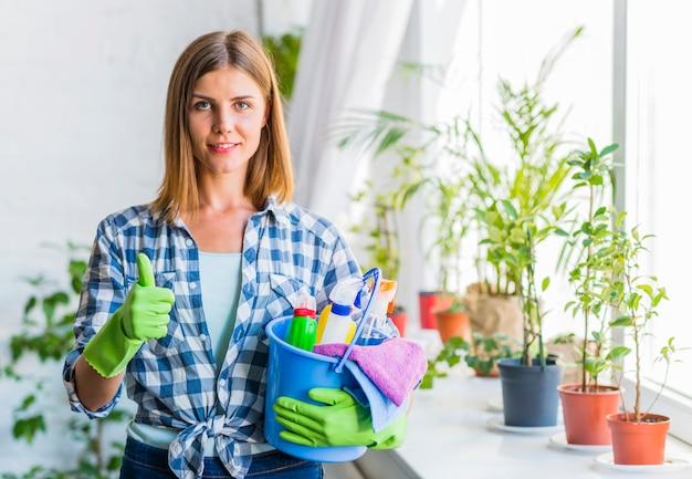 Retrato de una mujer joven sonriente con el cubo de equipos de limpieza que gesticulan los pulgares para arriba