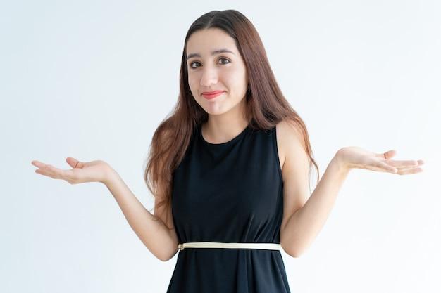 Retrato de mujer joven sonriente encogiéndose de hombros