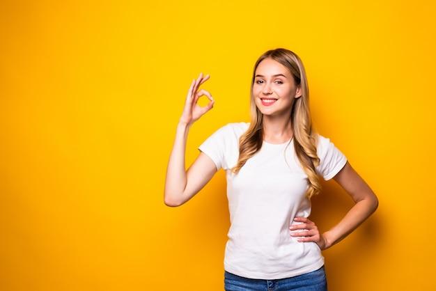 Retrato de mujer joven sonriente espacio de copia lateral aceptable aislado en la pared amarilla.