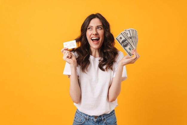 Retrato de mujer joven sonriente feliz contenta posando aislada sobre pared amarilla con dinero y tarjeta de débito.