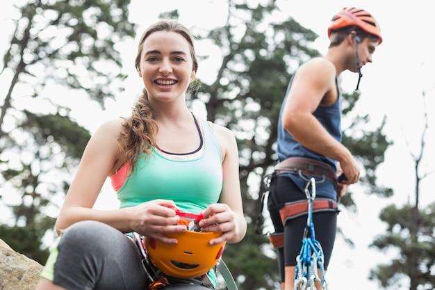 Retrato de mujer joven sonriente con hombre en roca