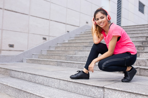 Retrato de mujer joven sonriente hunkering en auriculares al aire libre