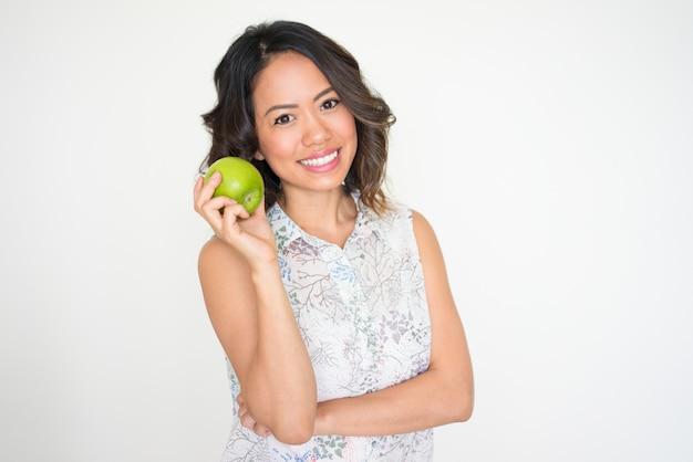 Retrato de mujer joven sonriente con manzana
