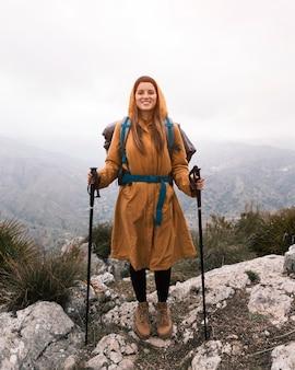 Retrato de una mujer joven sonriente con la mochila que sostiene el palillo del senderismo que se coloca en el top de la montaña