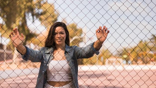 Retrato de una mujer joven sonriente de pie detrás de la valla