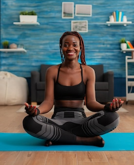 Retrato de mujer joven sonriente practicando yoga en casa sentado en posición de loto en la estera meditando, practicando la atención plena
