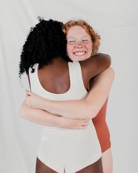 Retrato de una mujer joven sonriente que abraza a su amigo africano contra el contexto gris