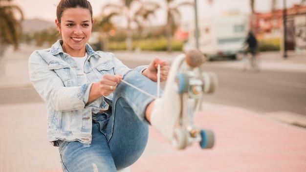 Retrato de una mujer joven sonriente que ata el cordón blanco del patín de ruedas en la calle